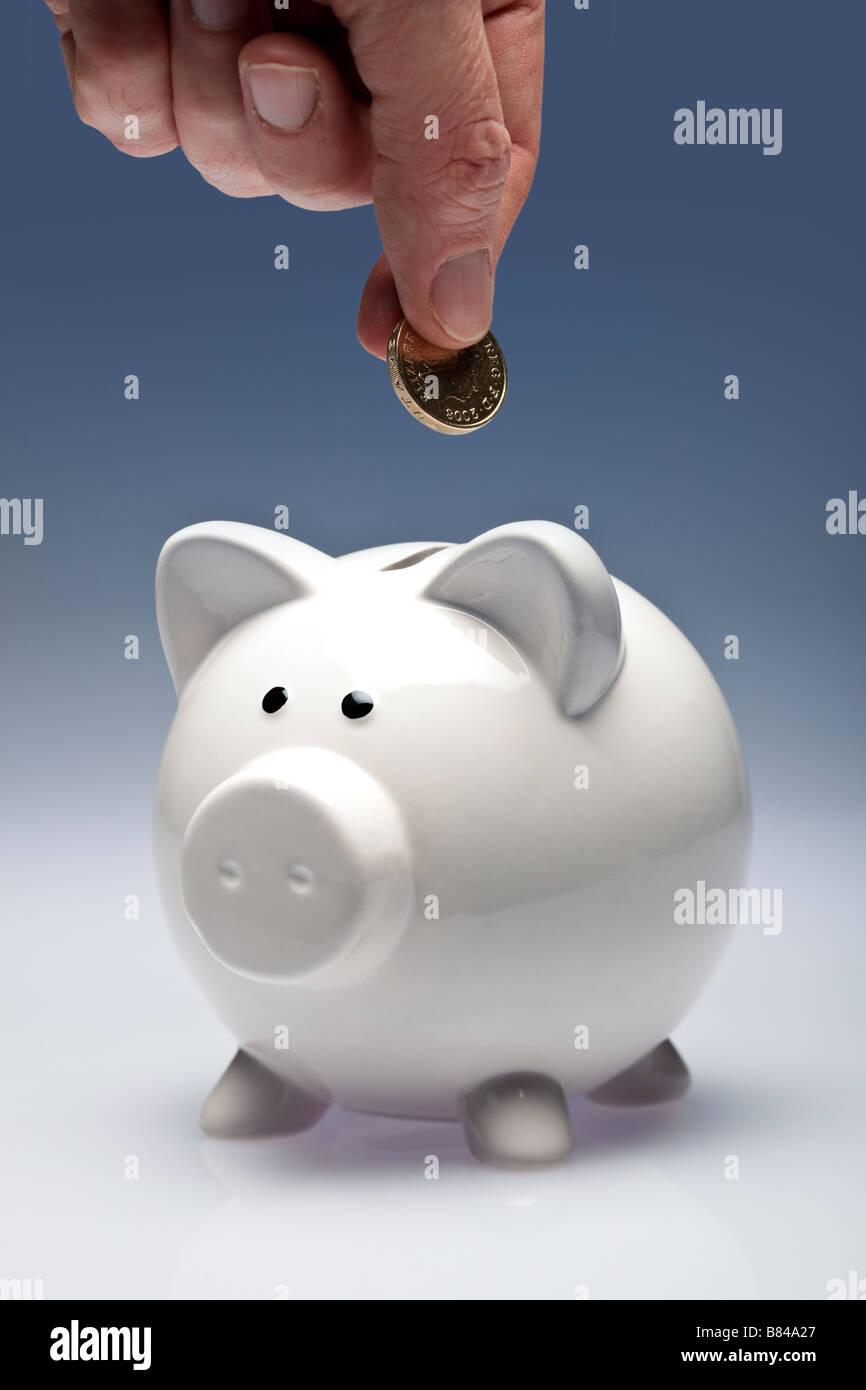 Sparschwein mit Fingern, eine Münze in Stockbild