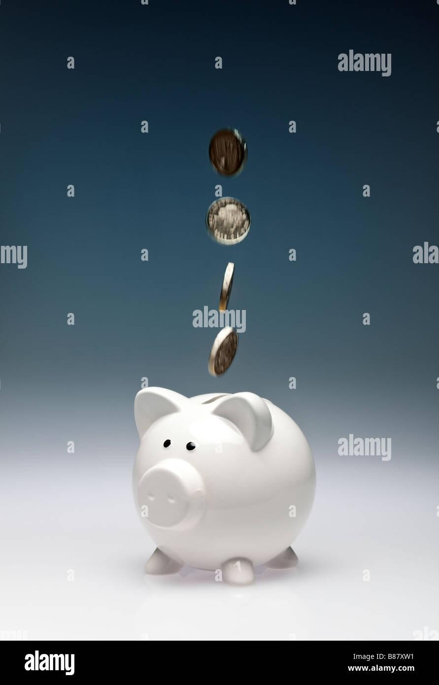 Konzept-Finanzen sparen - Münzen Pfund fallen in ein Sparschwein - studio Stockbild