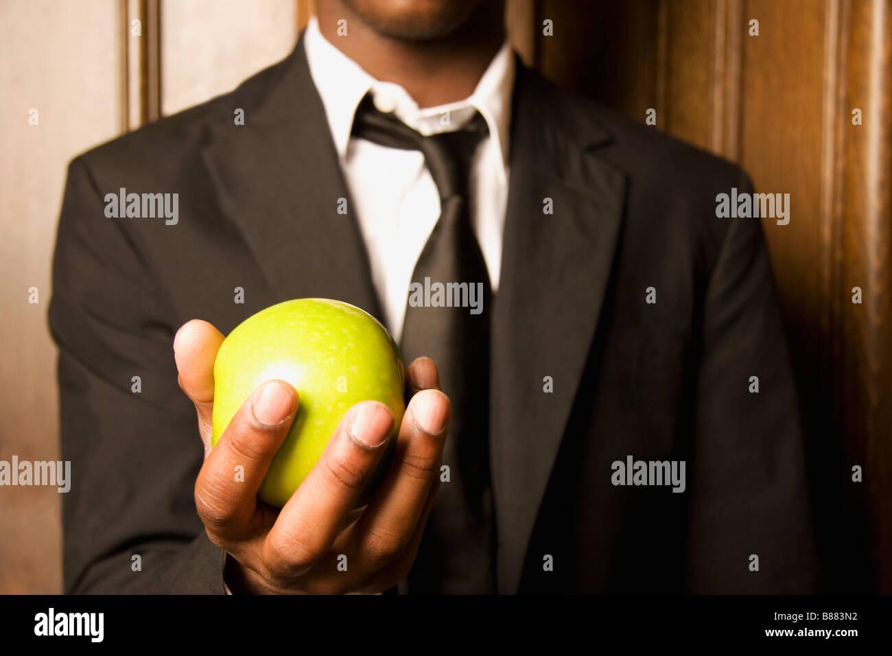 Mann hält einen Apfel Stockbild