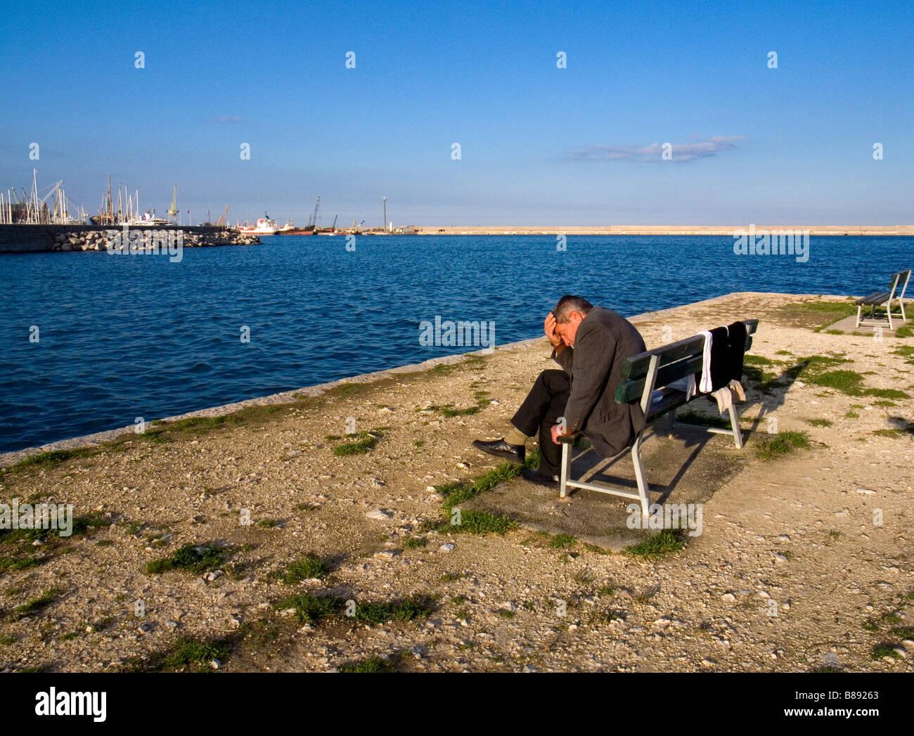 Mann sitzt auf einer Bank entlang des Yachthafens Palermo Sizilien Italien Stockbild