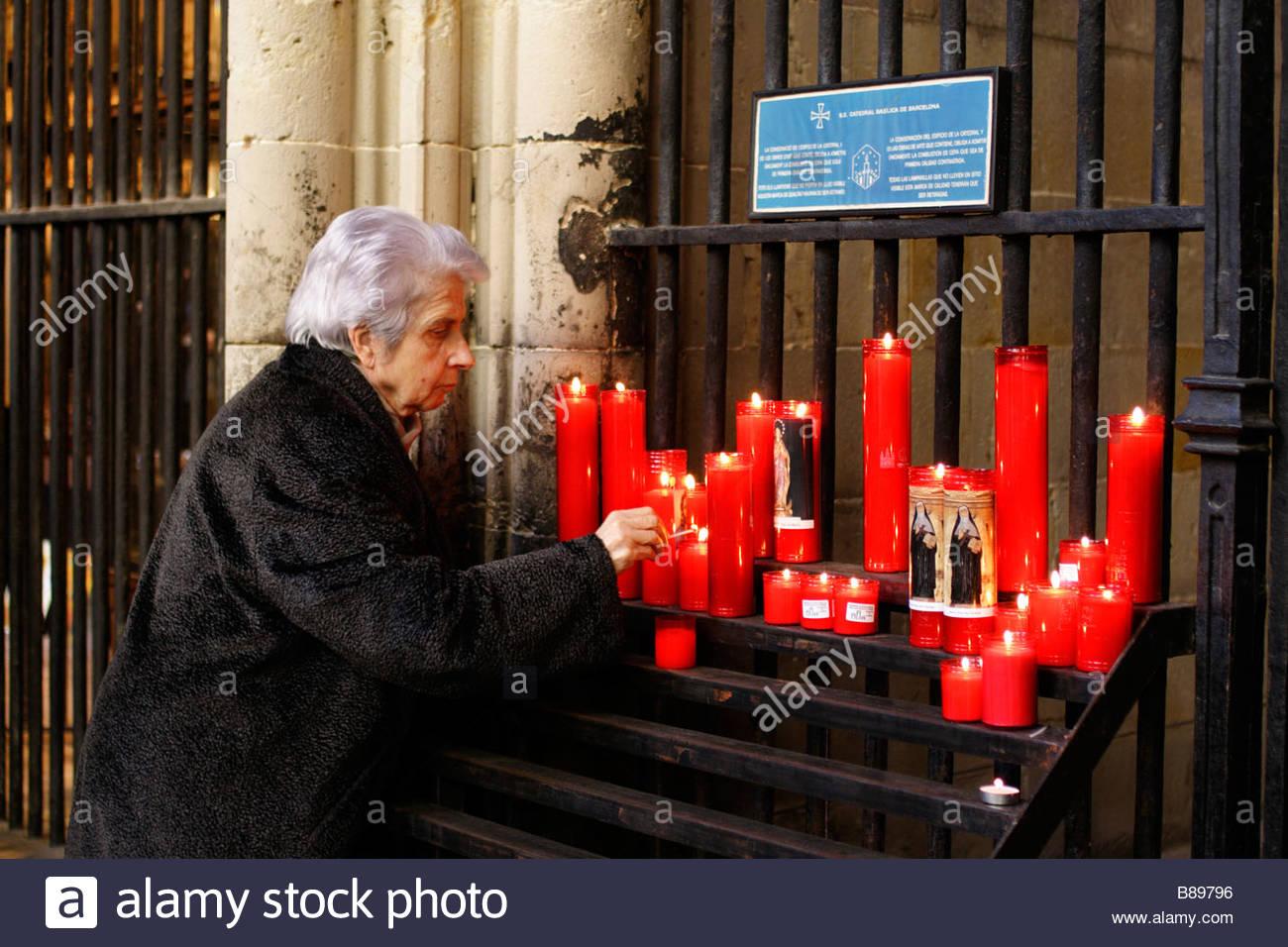 Ältere Frau Anzünden einer Kerze vor einer Kapelle im Kreuzgang der Kathedrale von Barcelona; Spanien Stockbild