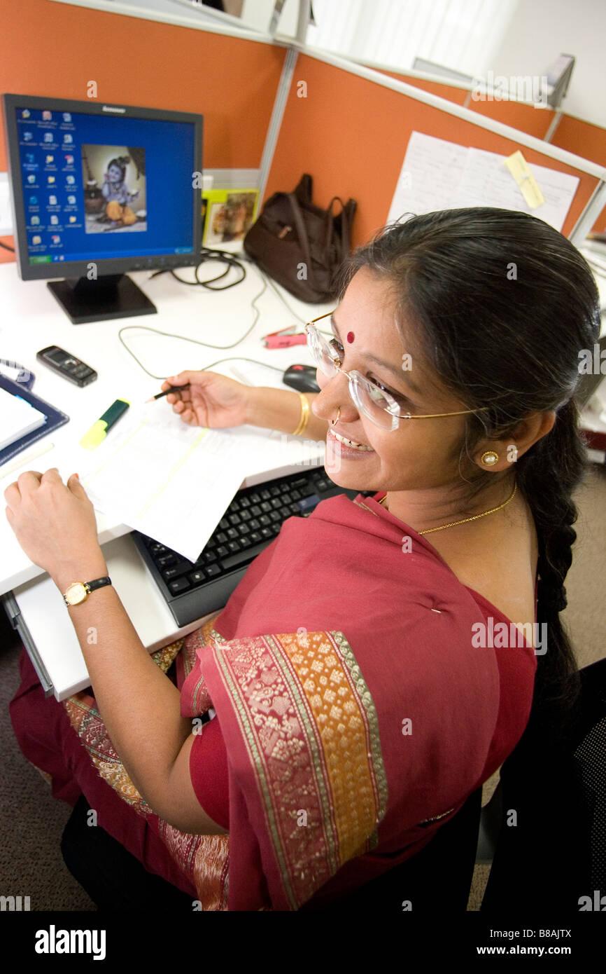 Eine Frau arbeitet an ihrem Computer in einem Großraumbüro in Bangalore, Indien. Stockfoto