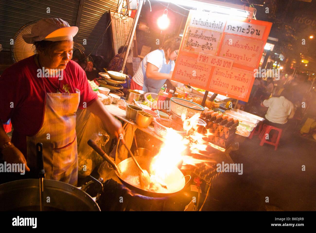 Frau unter Rühren braten Thai chinesisches Essen auf einem Nachtmarkt Thanon Yaowarat Road in Chinatown zentrale Stockbild