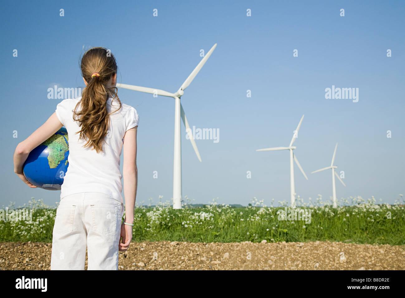 Mädchen mit Globe von Windkraftanlagen Stockbild