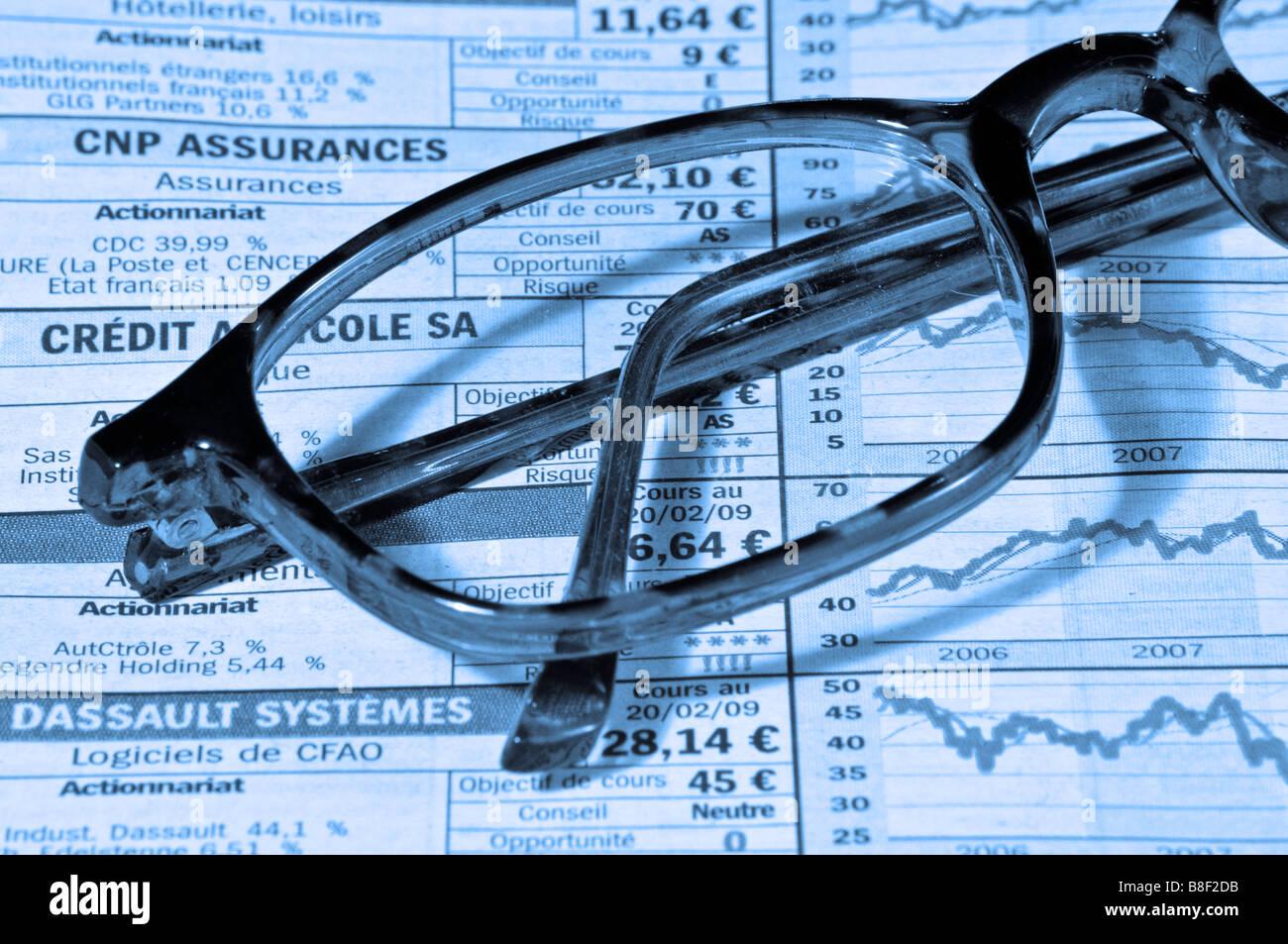 Brille aufsetzen einer Finanzzeitung Stockbild