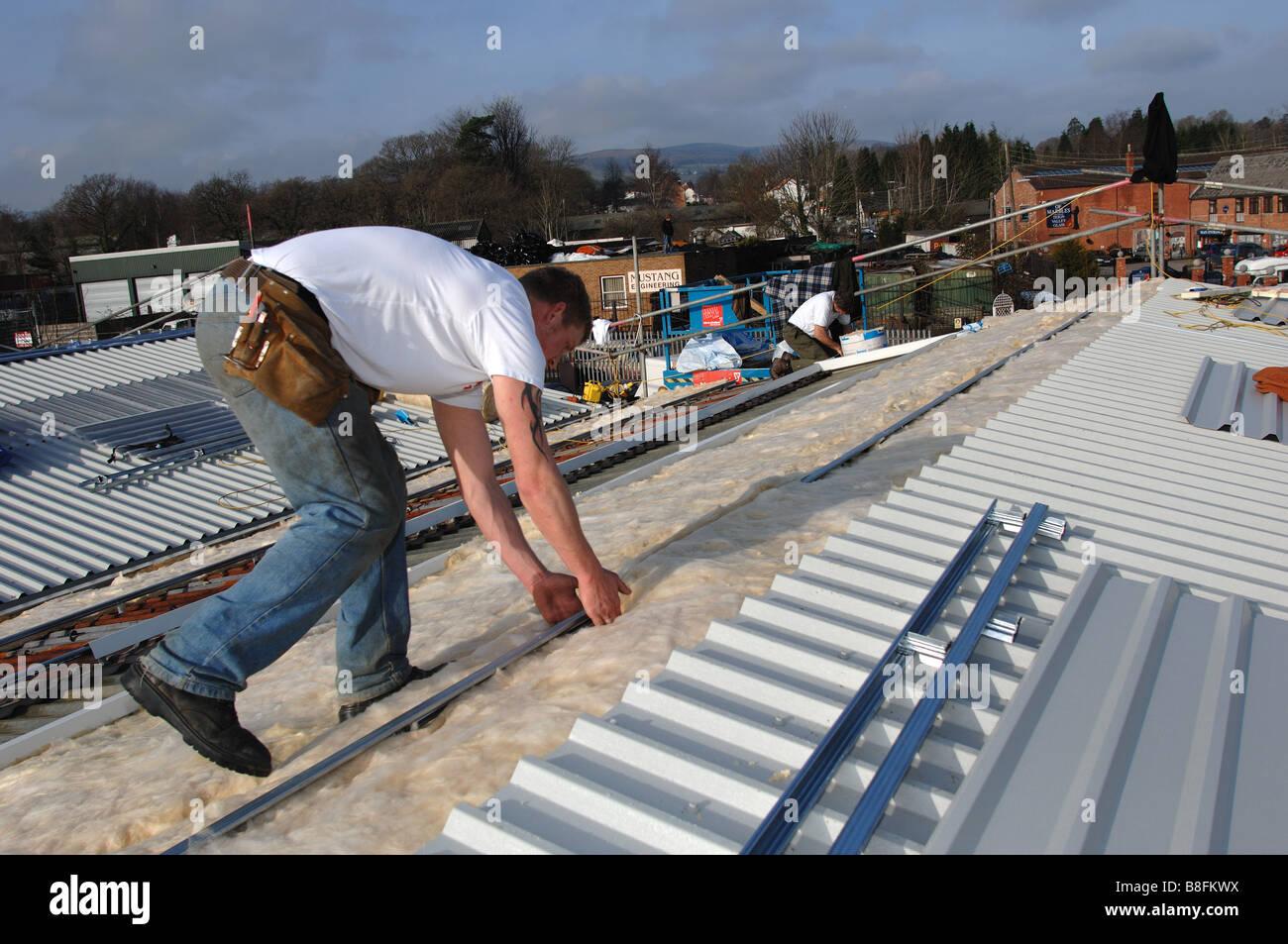 Auftragnehmer legen Sie zusätzliche Isolierung auf Dach einer Industriehalle in Bovey Tracey Devon Stockbild