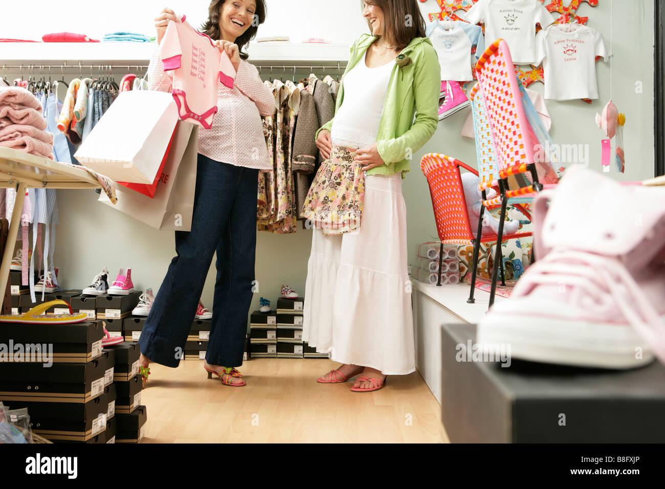 ae7e9ca2d6 Zwei schwangere Frauen einkaufen, Blick auf Babyausstattung, lachen  Stockbild