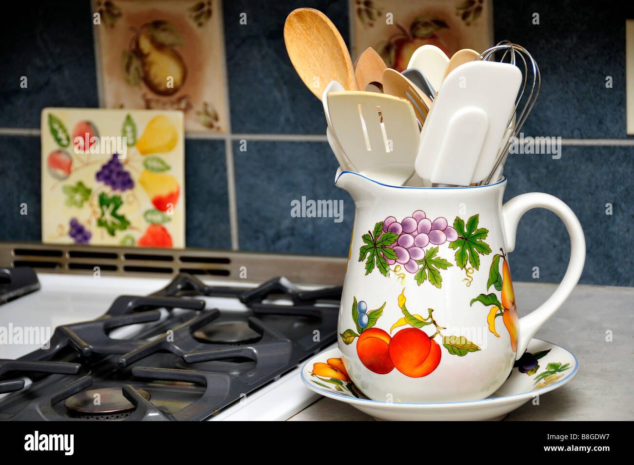 Eine große, eingerichtete Krug holding Küchengeräte neben einem Gas ...