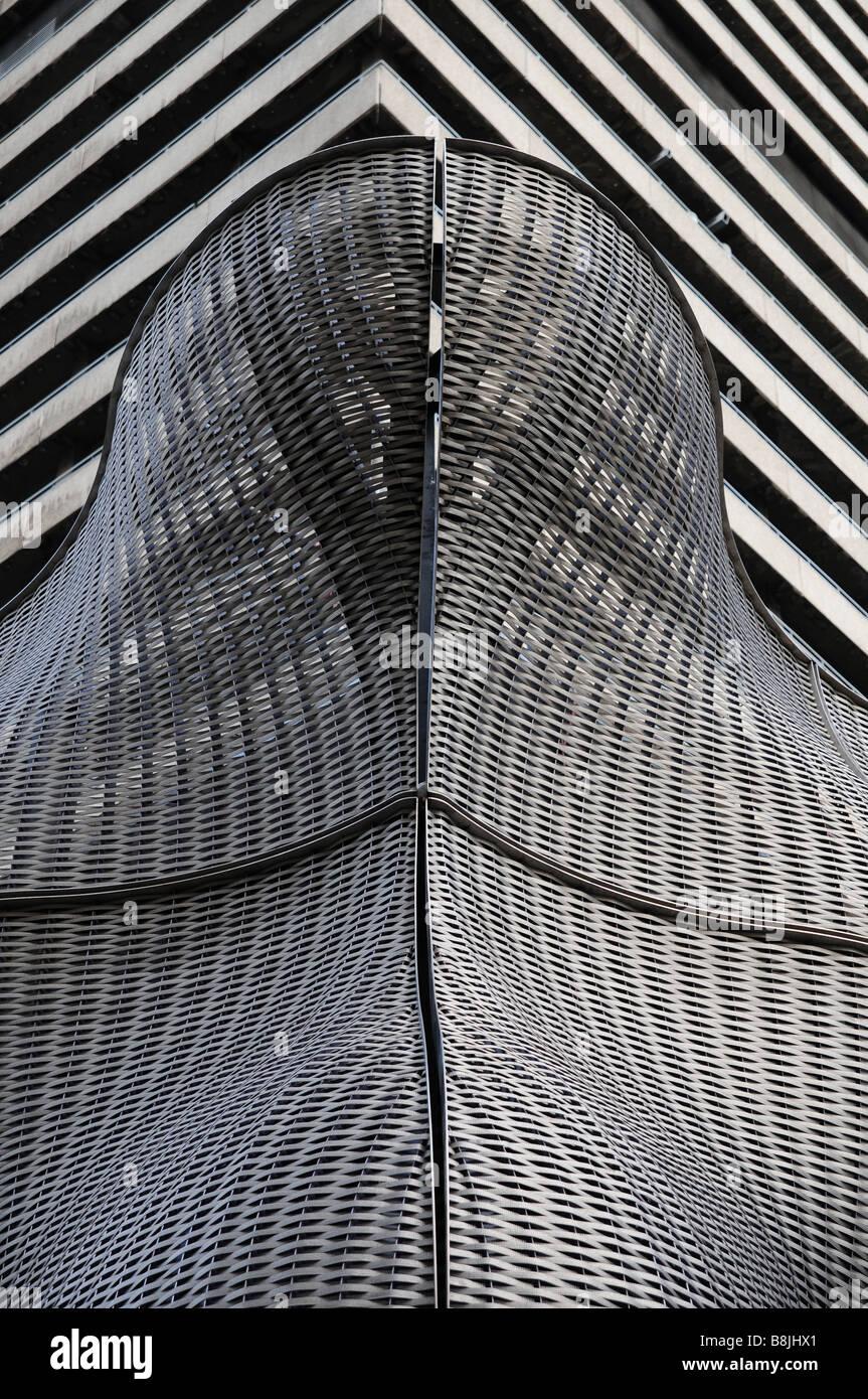 Eine geschwungene zeitgenössische 21. Jahrhundert Struktur vor eine stereotype geraden 1960 oder 1970 des Hochhauses. Stockbild
