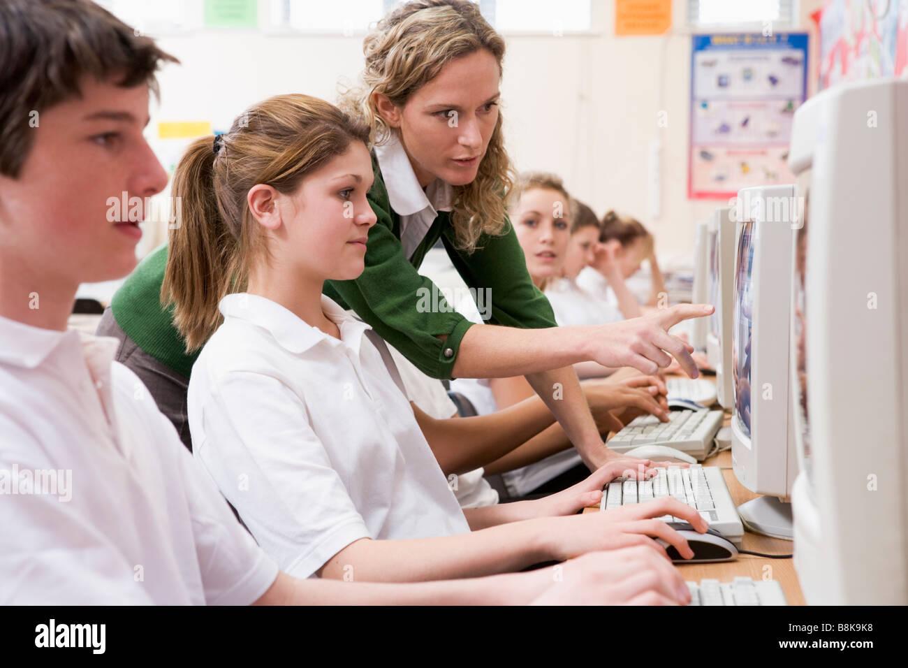 Studenten arbeiten an Computerarbeitsplätzen mit Lehrer Stockfoto
