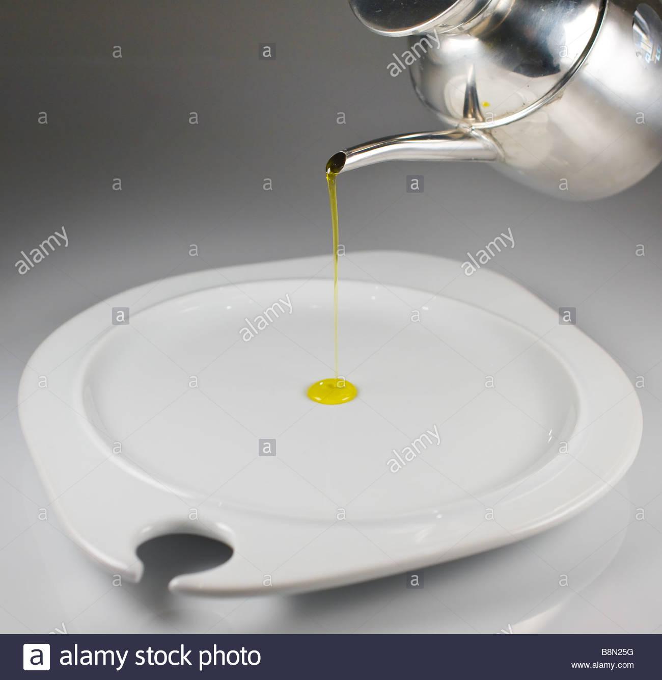 Gießen Olivenöl auf einem Teller Stockbild
