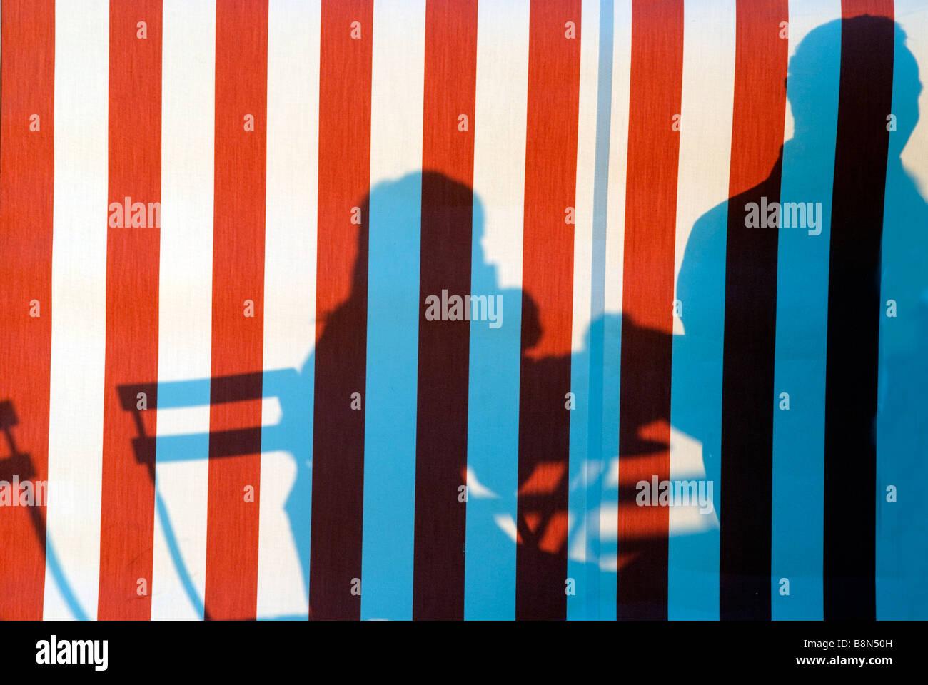 Silhouetten von Menschen im Café auf rot-weiß gestreiften Zelt in Sonne projiziert Stockbild