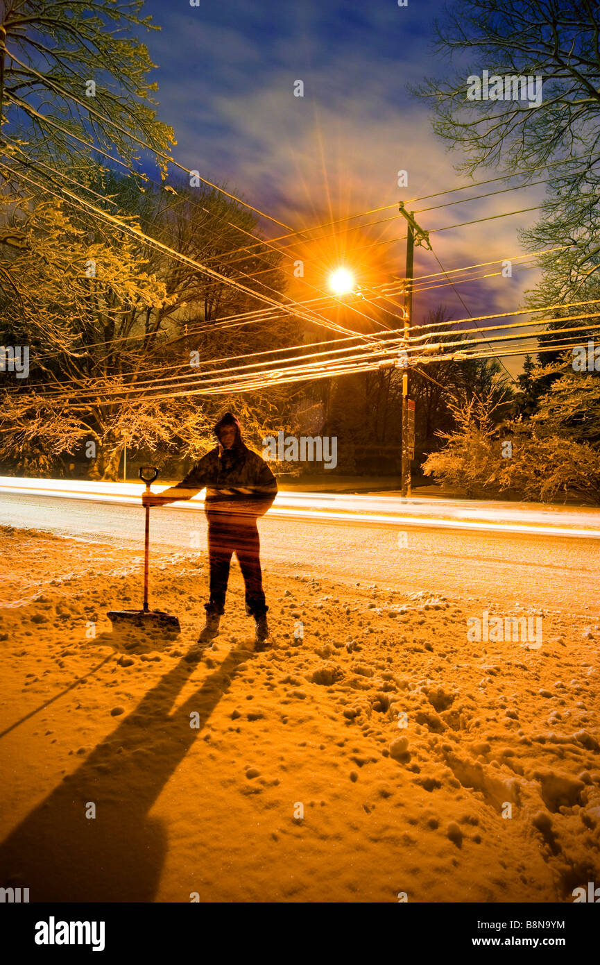 Mann Schneeschaufeln bei Sonnenaufgang mit Straßenlaterne hinter ihm, USA Stockbild
