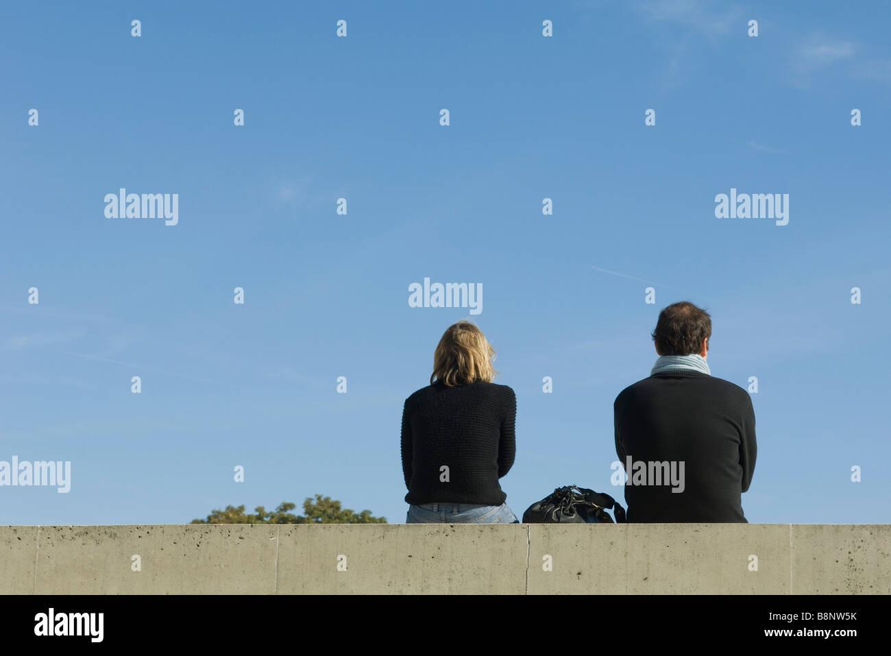 Paar sitzt auf Sims, Rückansicht Stockbild