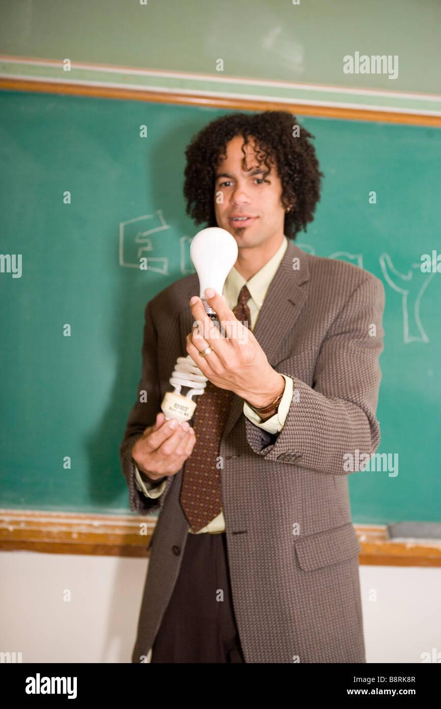 Lehrer in amerikanische Klassenzimmer hält Energie effiziente kompakte Leuchtstoff Glühlampe und herkömmlichen Stockbild