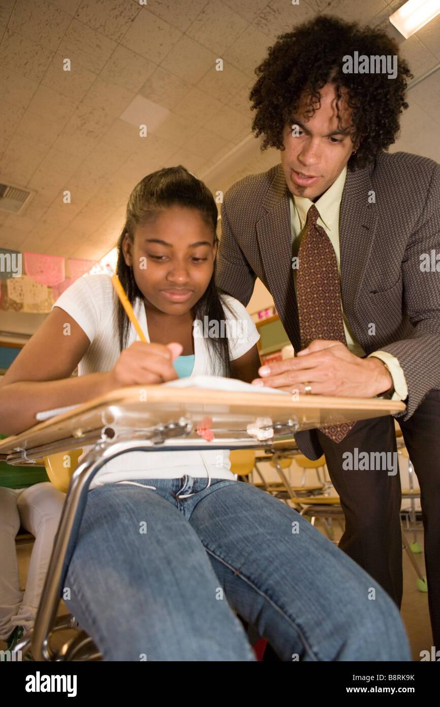 afrikanische amerikanische mittlere Schullehrer hilft Teenager-Studentin eine mathematisches Problem in der Klasse, Stockbild