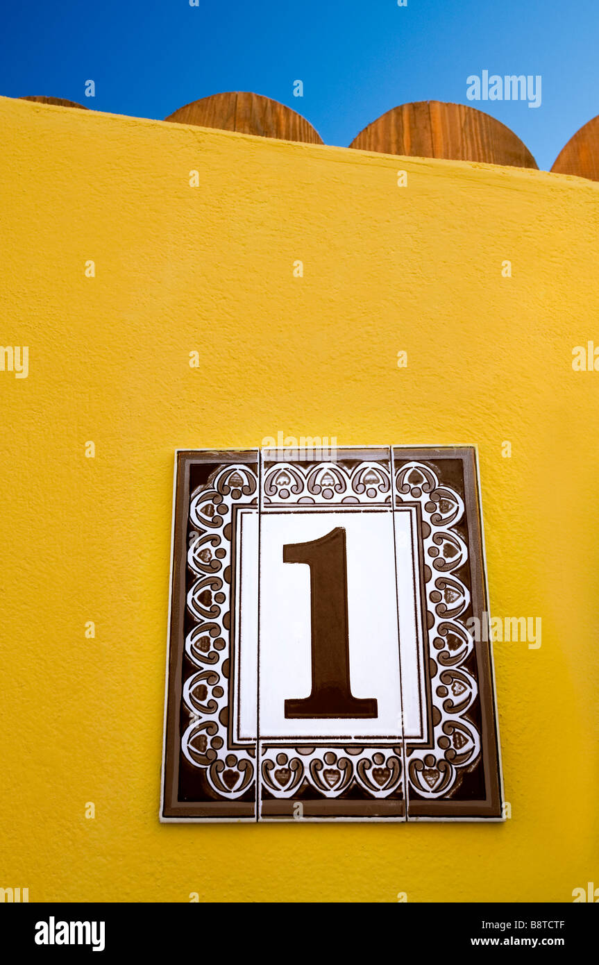 Keramik schwarz & weiße Nummer 1 auf gelbe Wand außerhalb sonnigen Urlaub Urlaub mediterrane villa Stockbild