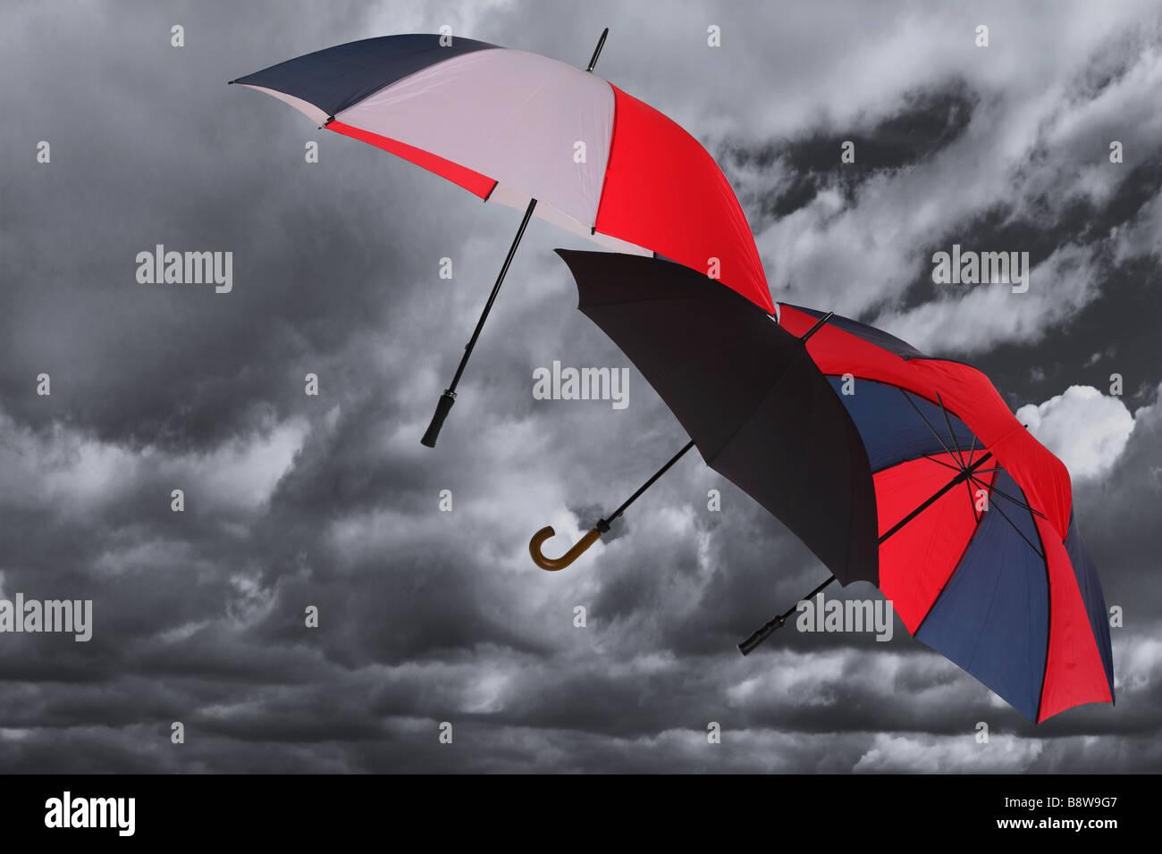 Drei Regenschirme über dunkle stürmische bewölktem Himmel geblasen Stockbild