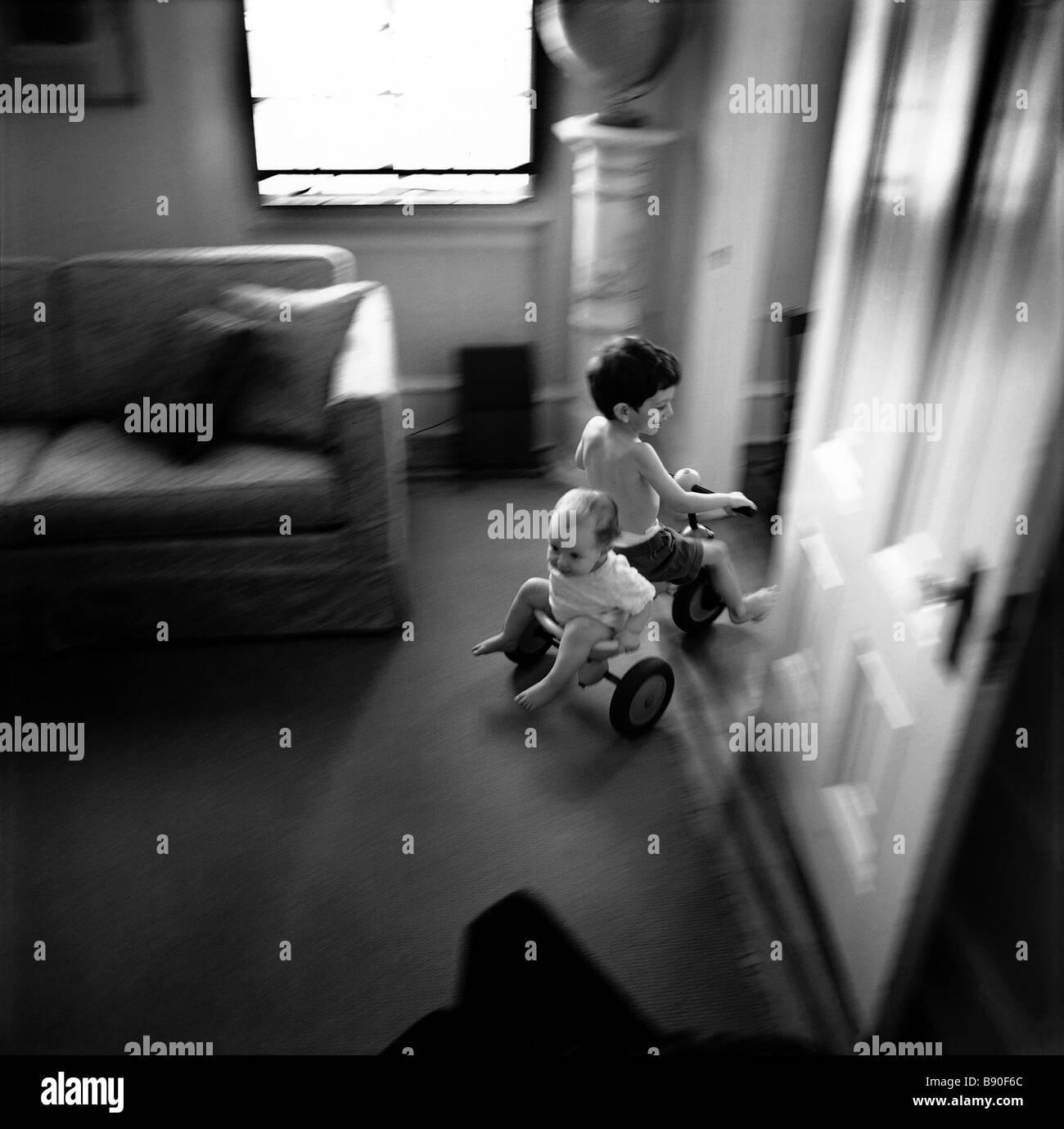 FL2671, NICK KELSH; Kinder Dreirad fahren durch Haus Stockbild