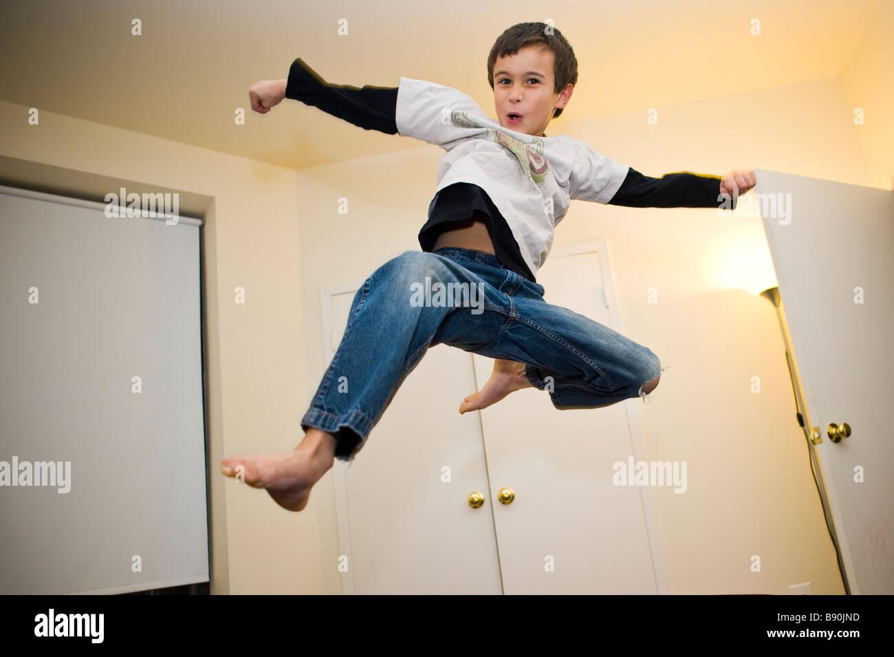 Ein kleiner Junge einen fliegenden smash Kick zu tun Stockbild