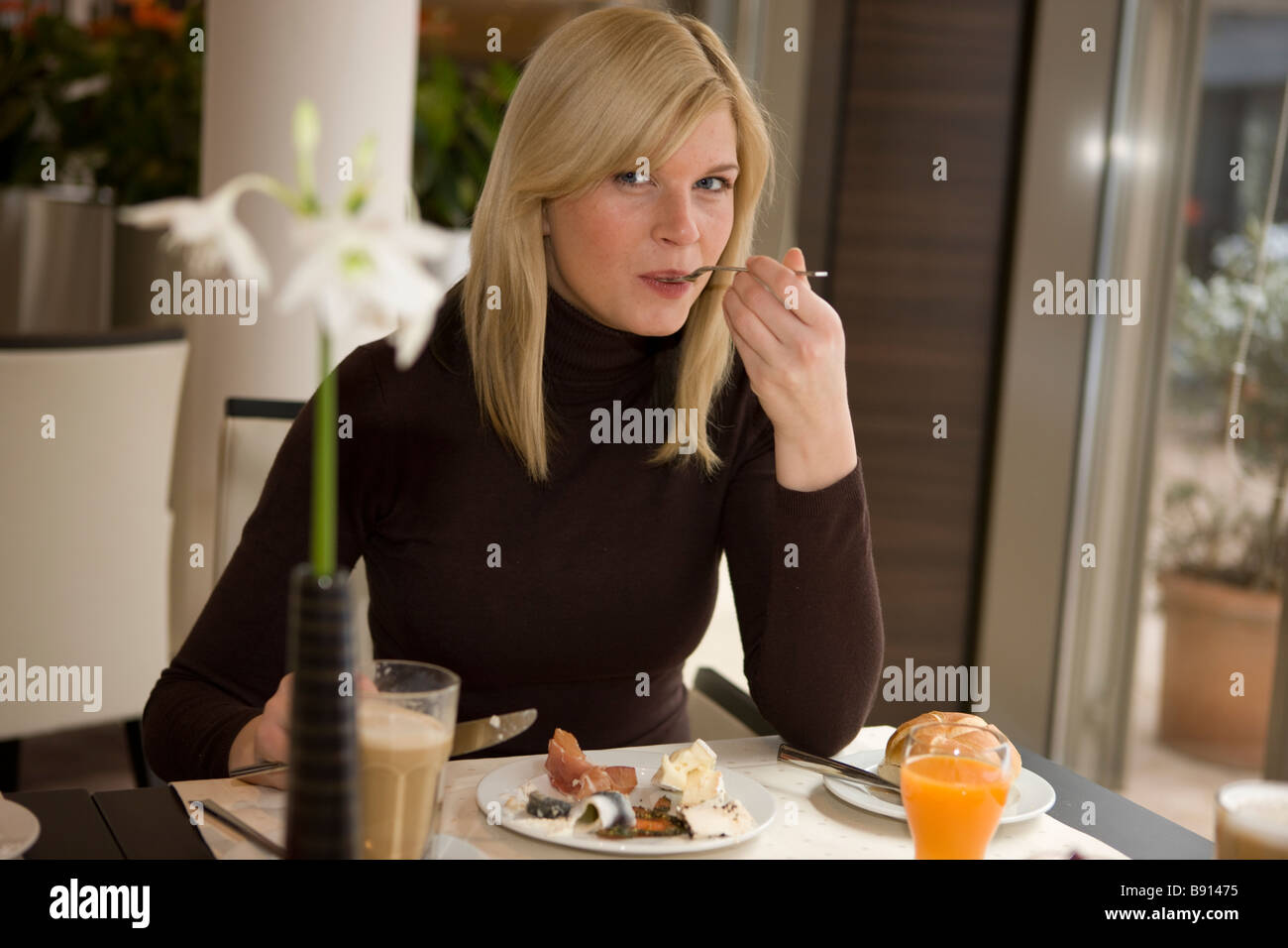 Frau Im Hotel Beim Fruehstuecken Mit Gabel Im Mund, Gedeckter Tisch Im Vordergrund Mit Kaffee, Saft. Stockbild