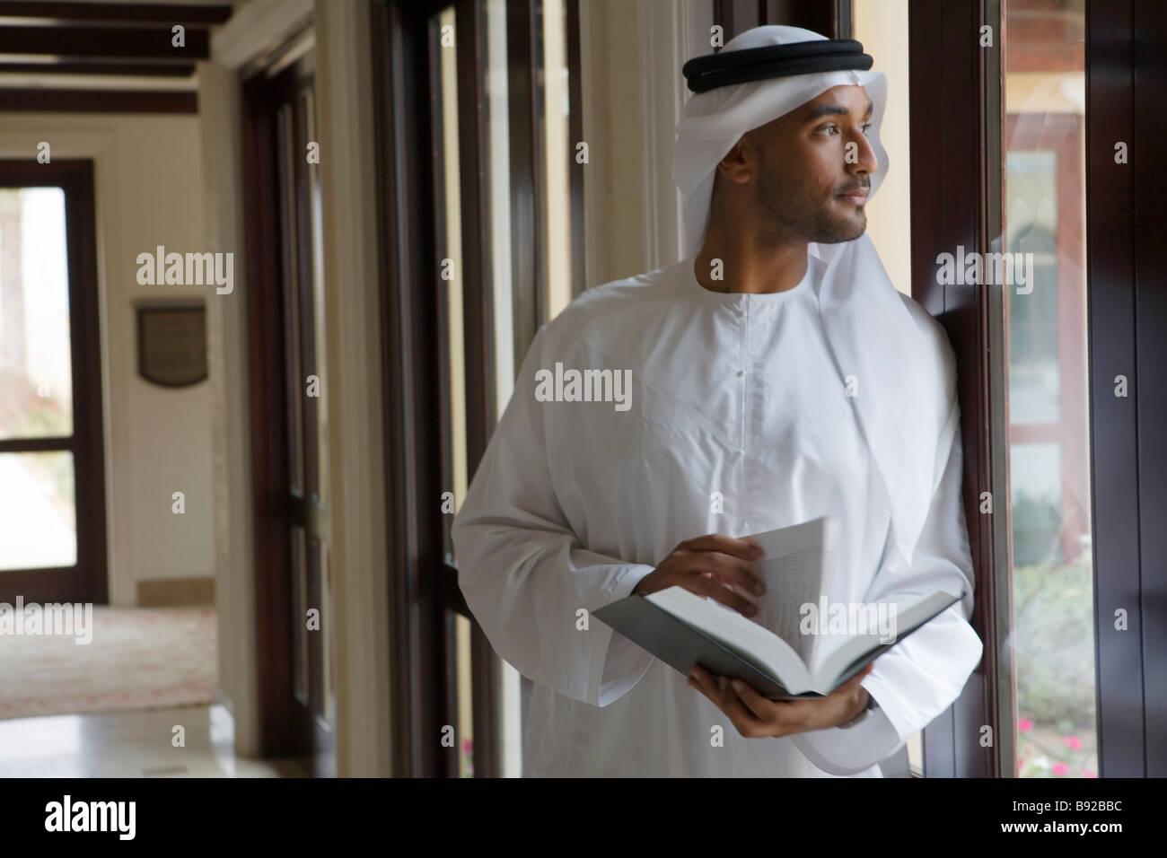 Arabische Mann schaut aus einem Fenster ein Buch hält Stockbild