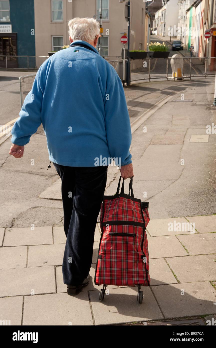 Rückansicht von hinten von einem älteren Mann zu Fuß nach Hause mit seinen Einkaufsmöglichkeiten Stockbild