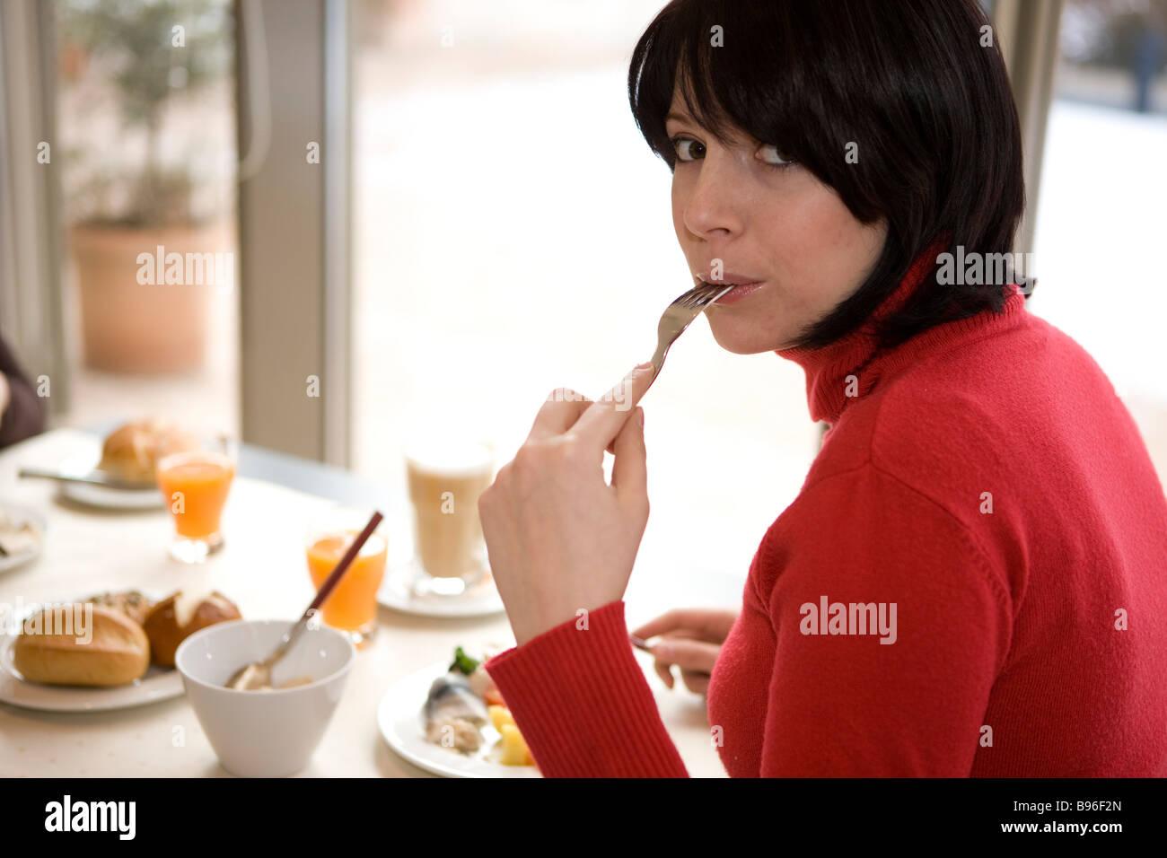 Frau bin Tisch Hut Gabel Im Mund Und isst Stockbild