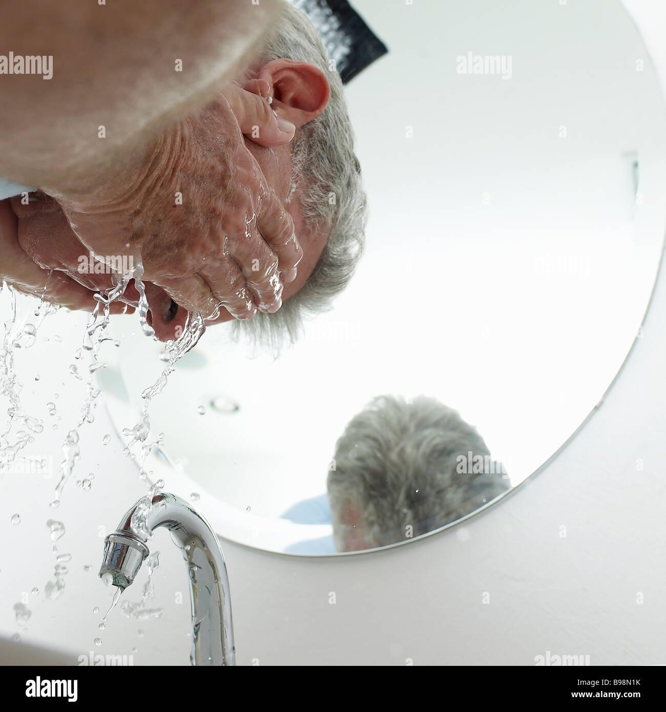 reifer Mann waschen Gesicht Stockbild