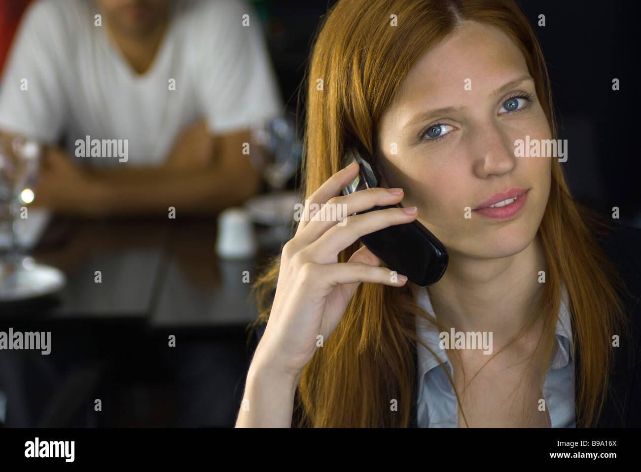 Frau mit Handy zum Ohr, in die Kamera Lächeln Stockfoto