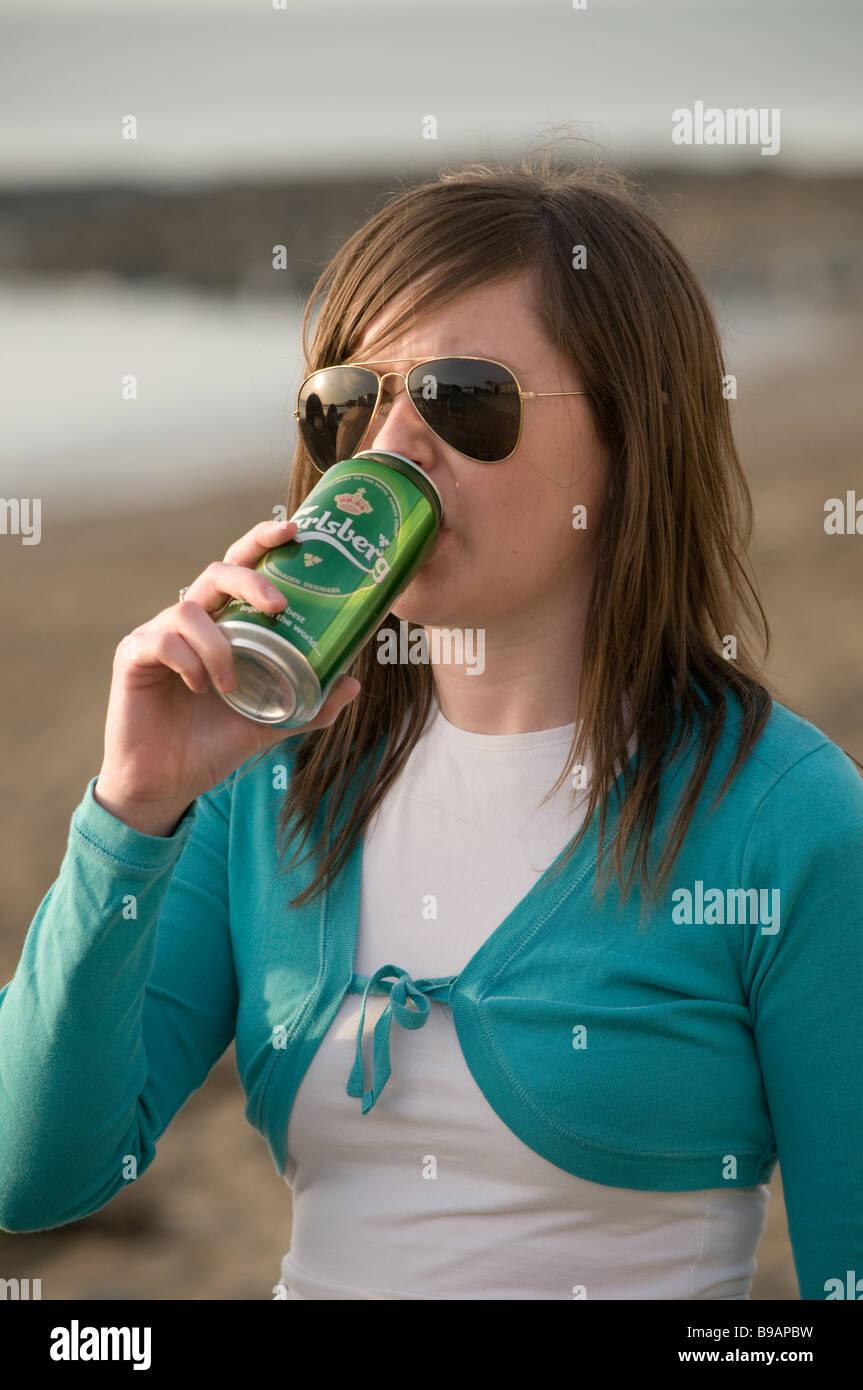 Ein junges Mädchen Studentin trinken eine Dose Carlsberg Lagerbier Alkohol außerhalb UK Stockfoto