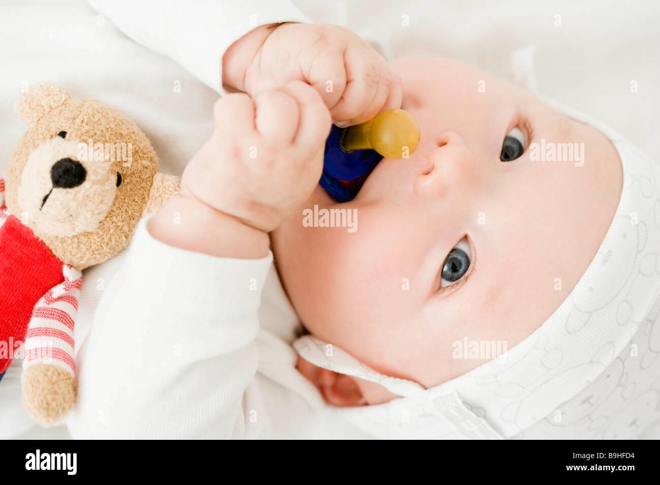 Baby knabbert an Schnuller Stockbild