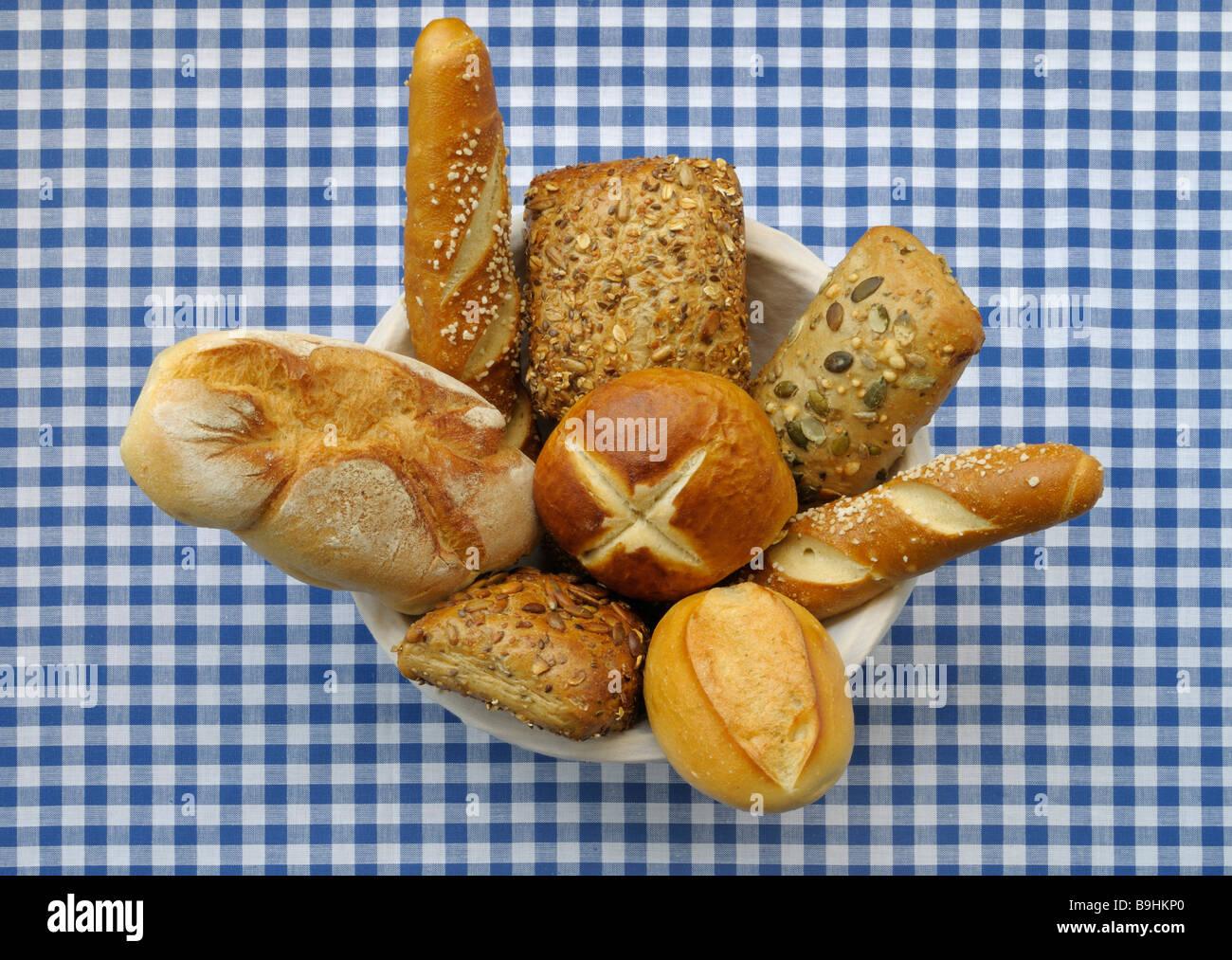 Brotkorb mit verschiedenen Arten von Rollen und Lauge gefüllt rollt auf einer blau-weißen aufgegebenes Stockbild