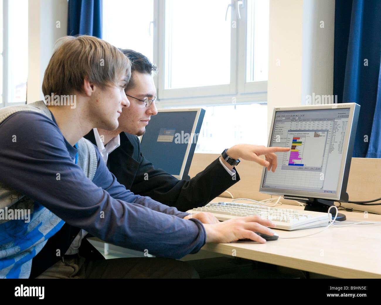 Jugendliche, die an einem Computer arbeiten mit Grafiken und Tabellen Stockbild