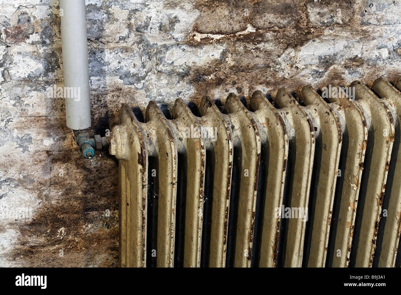 Alte Heizkörper alte heizkörper mit farbe abplatzt montiert an feuchten kellerwand