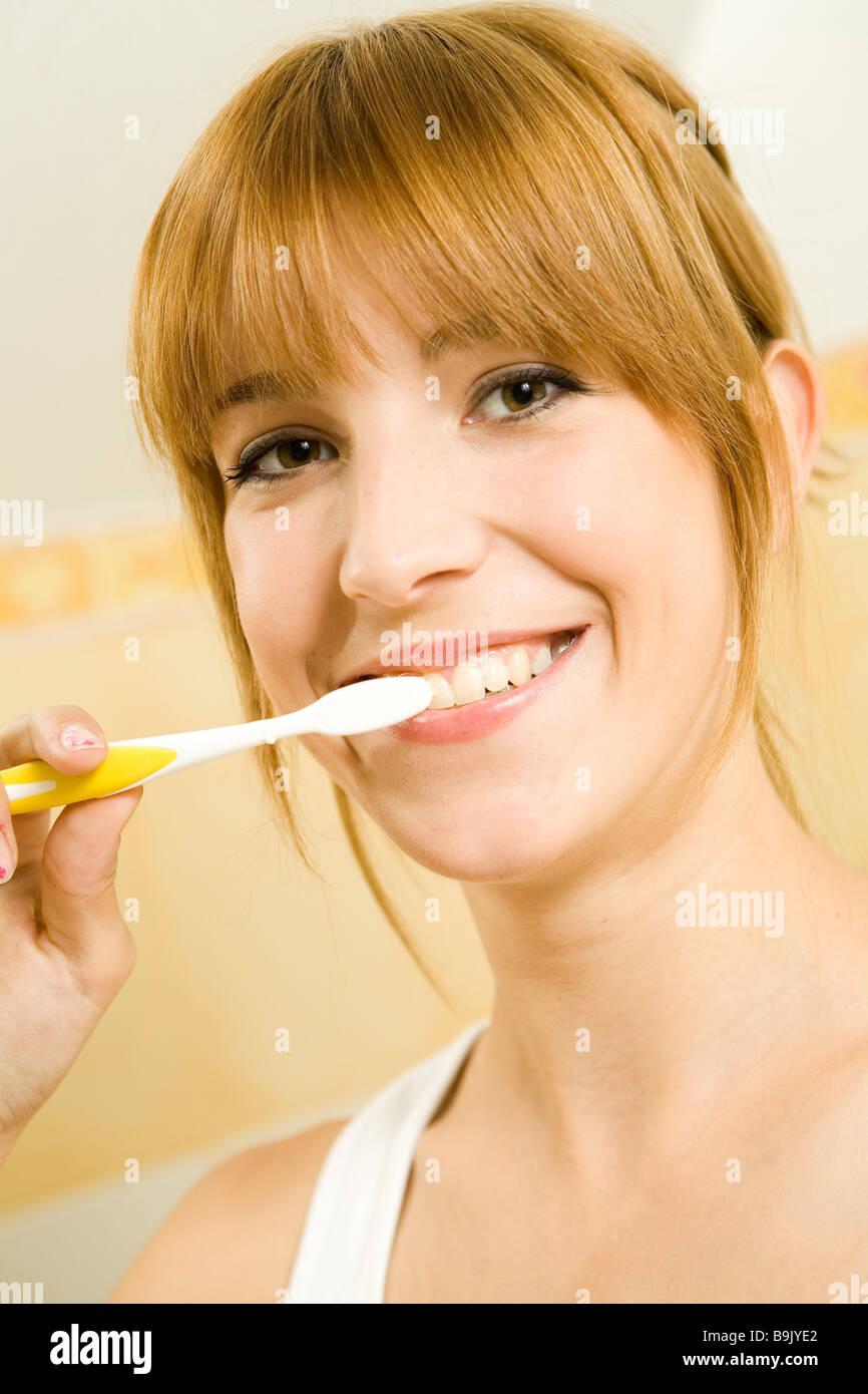 Junge Frau, die ihre Zähne putzen Stockbild