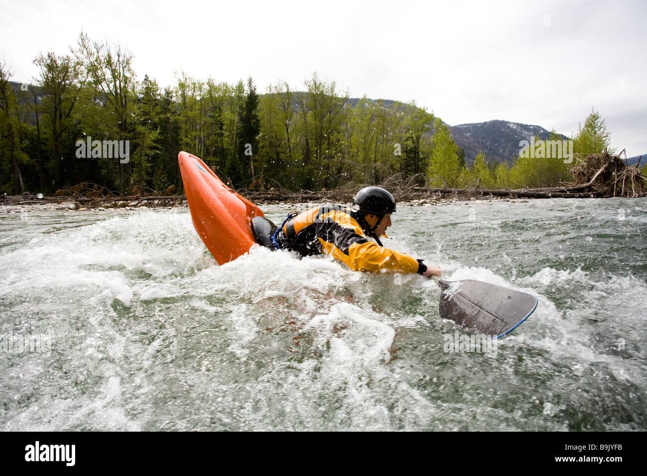 Ein Playboater genießt eine kleine Welle auf einem Fluss. Stockbild