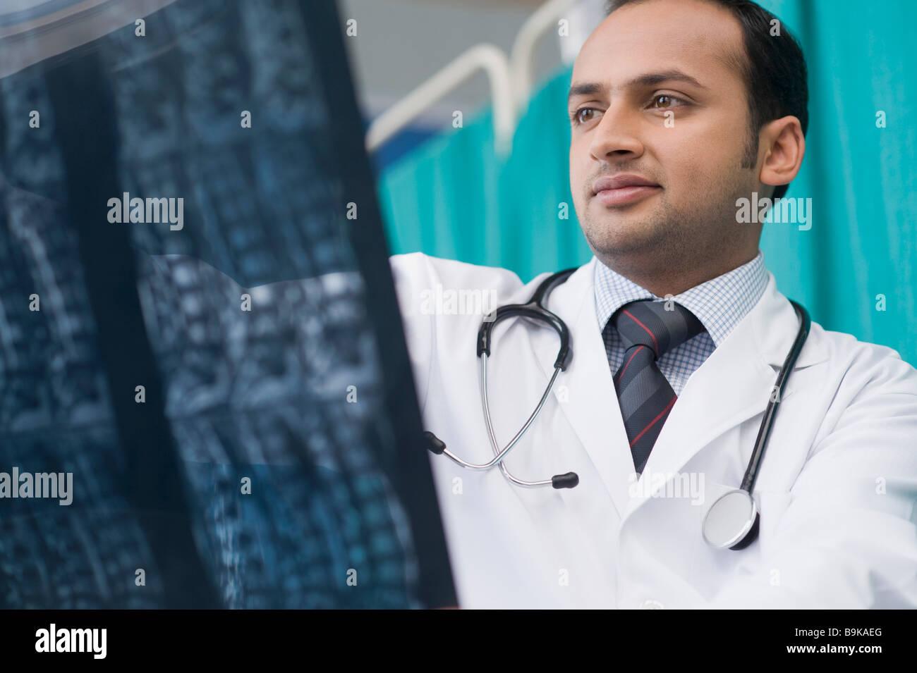 Arzt untersucht einen Röntgen-Bericht Stockfoto