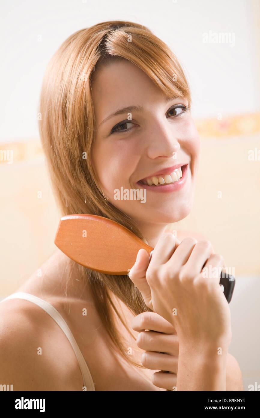 Junge Frau, die ihr Haar kämmen Stockbild