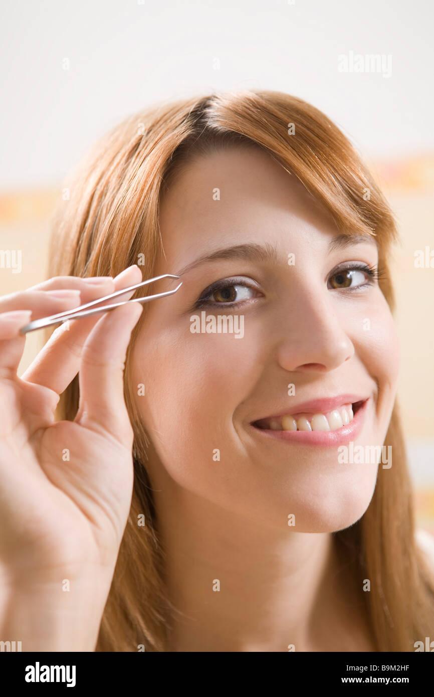 Junge Frau, die ihre Augenbrauen zupfen Stockbild