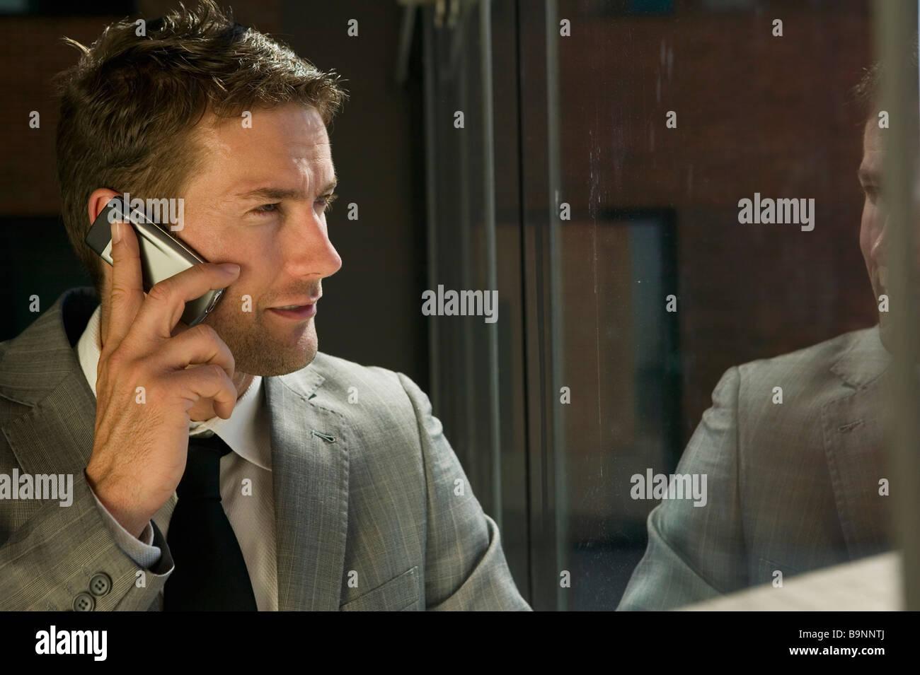 Porträt der Geschäftsmann gegenüber Fenster telefonieren mit Handy Stockbild
