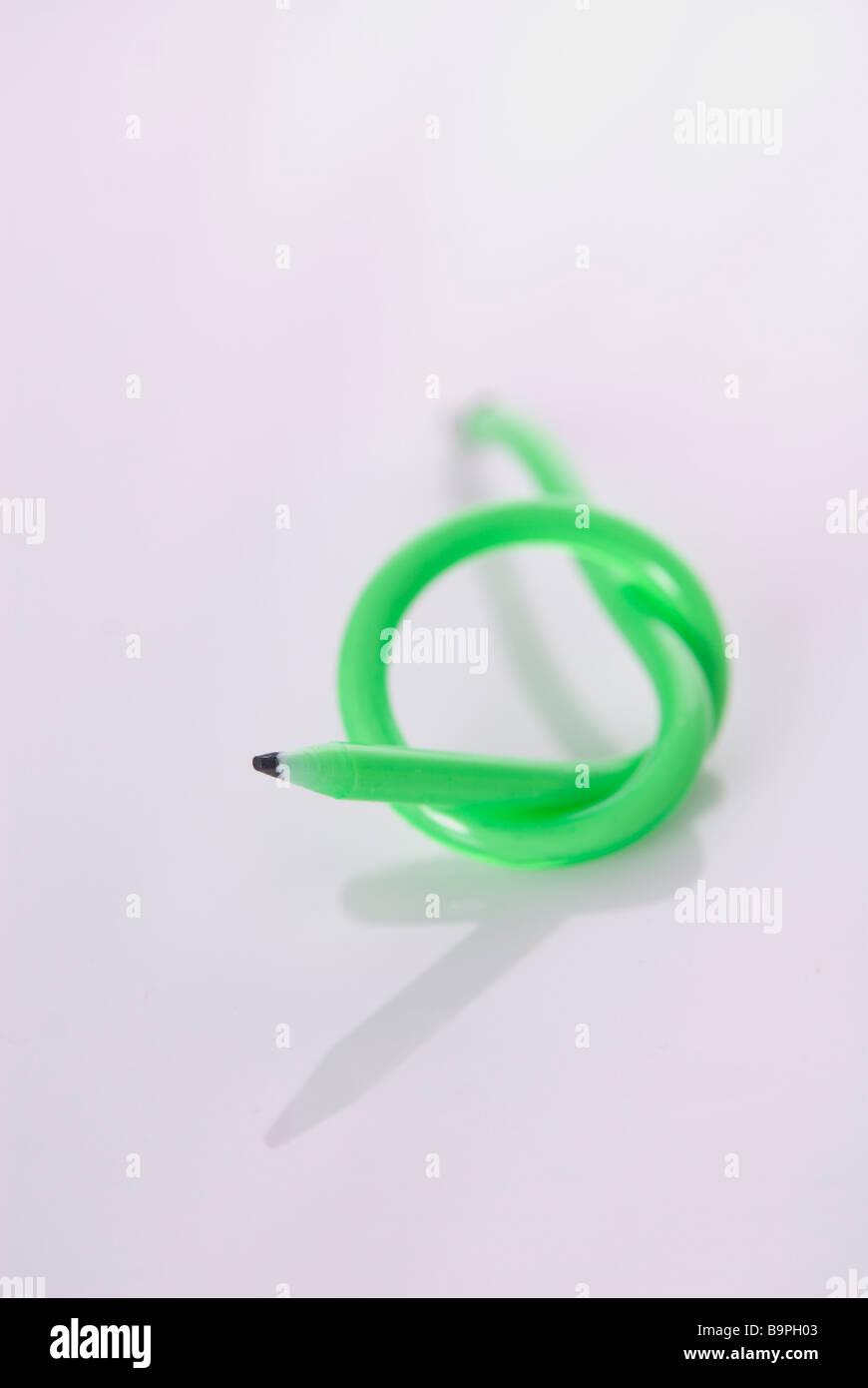 Grüne flexible Bleistift mit einem Knoten auf einem weißen Hintergrund Stockbild