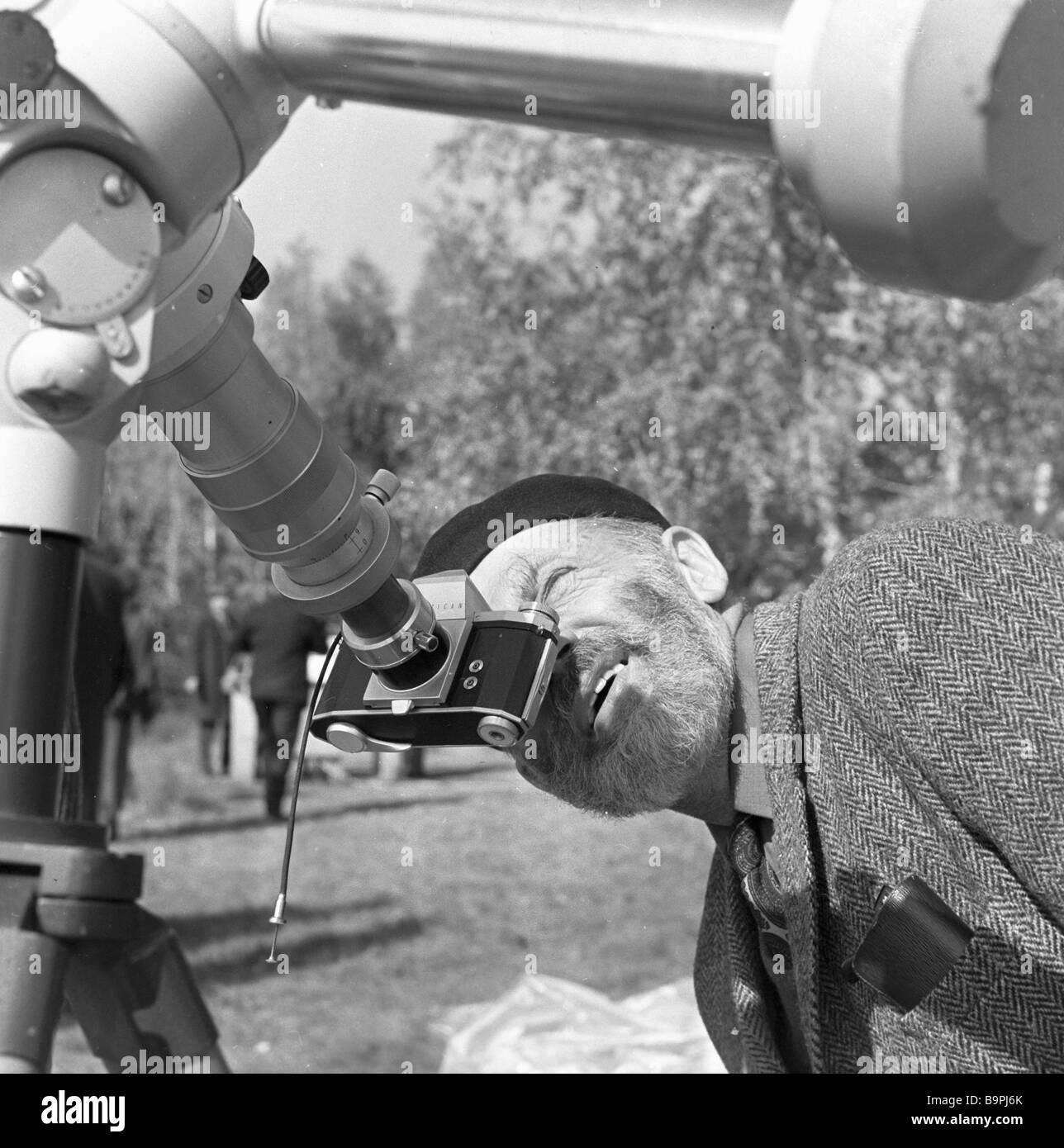 Ein niederländischer Wissenschaftler eine totale Sonnenfinsternis beobachten, durch ein Teleskop Stockbild