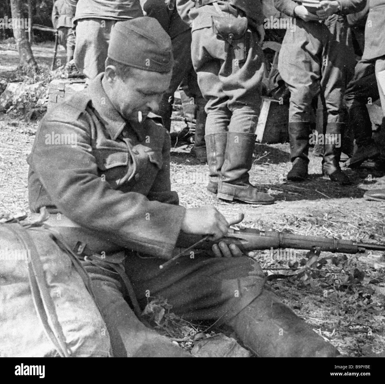 Ein Soldat des 1 Tschechische Korps reinigt seine Waffe Stockbild