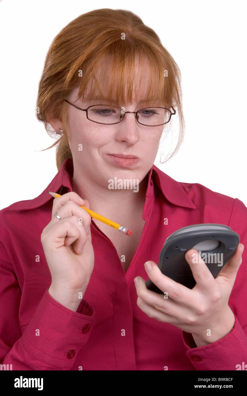 Eine Frau, die Stanzen Taschenrechner-Tasten mit einem Bleistift Stockbild