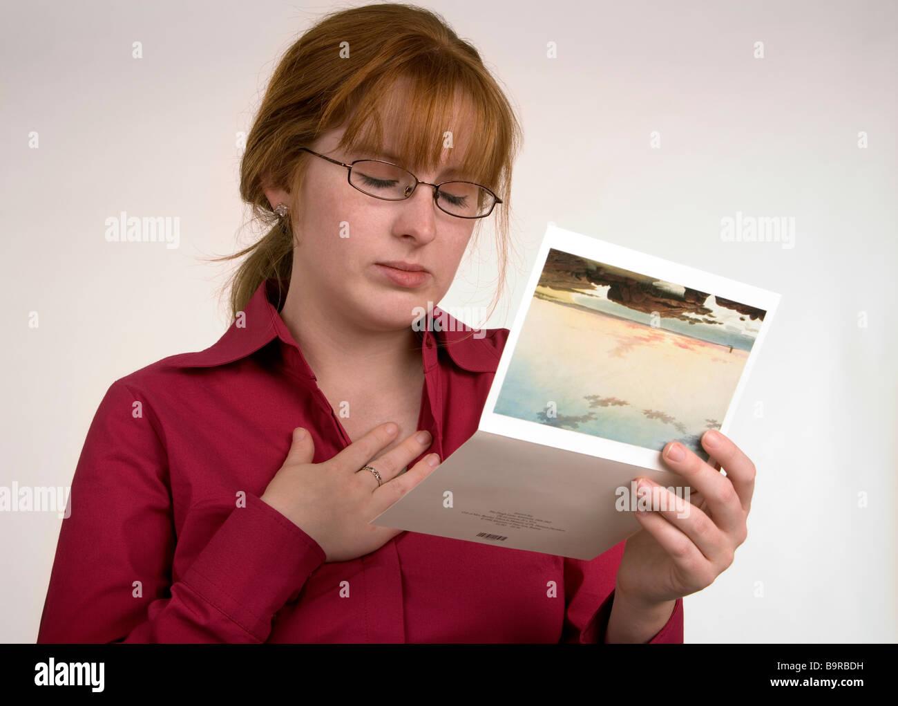 Eine Frau liest eine Karte, die einige Nachrichten übermittelt hat, die ihr traurig oder emotionale gemacht hat Stockfoto