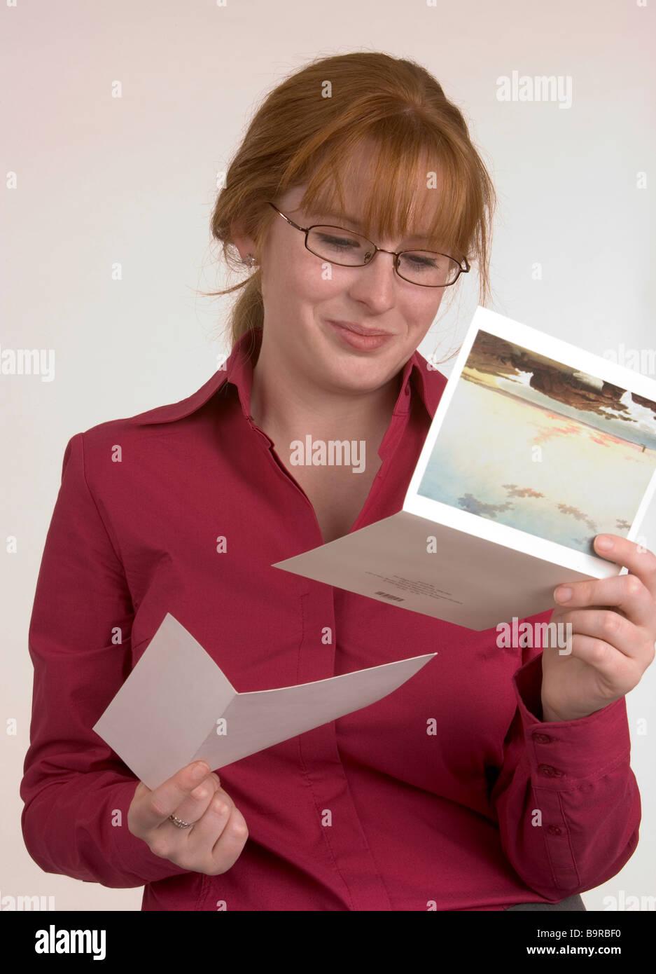 Eine Frau liest eine Karte, die einige frohe Botschaft übermittelt hat, die ihr Lächeln gemacht hat Stockbild
