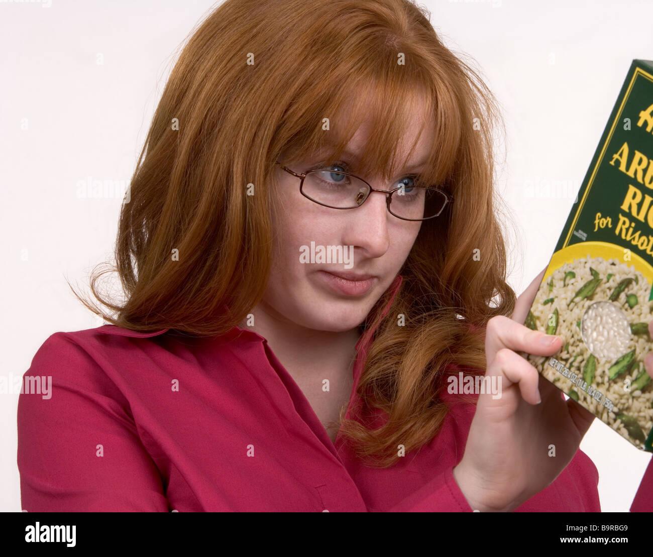 Eine Frau sorgfältig liest die Produktinformationen auf einem Lebensmittelpaket Stockbild