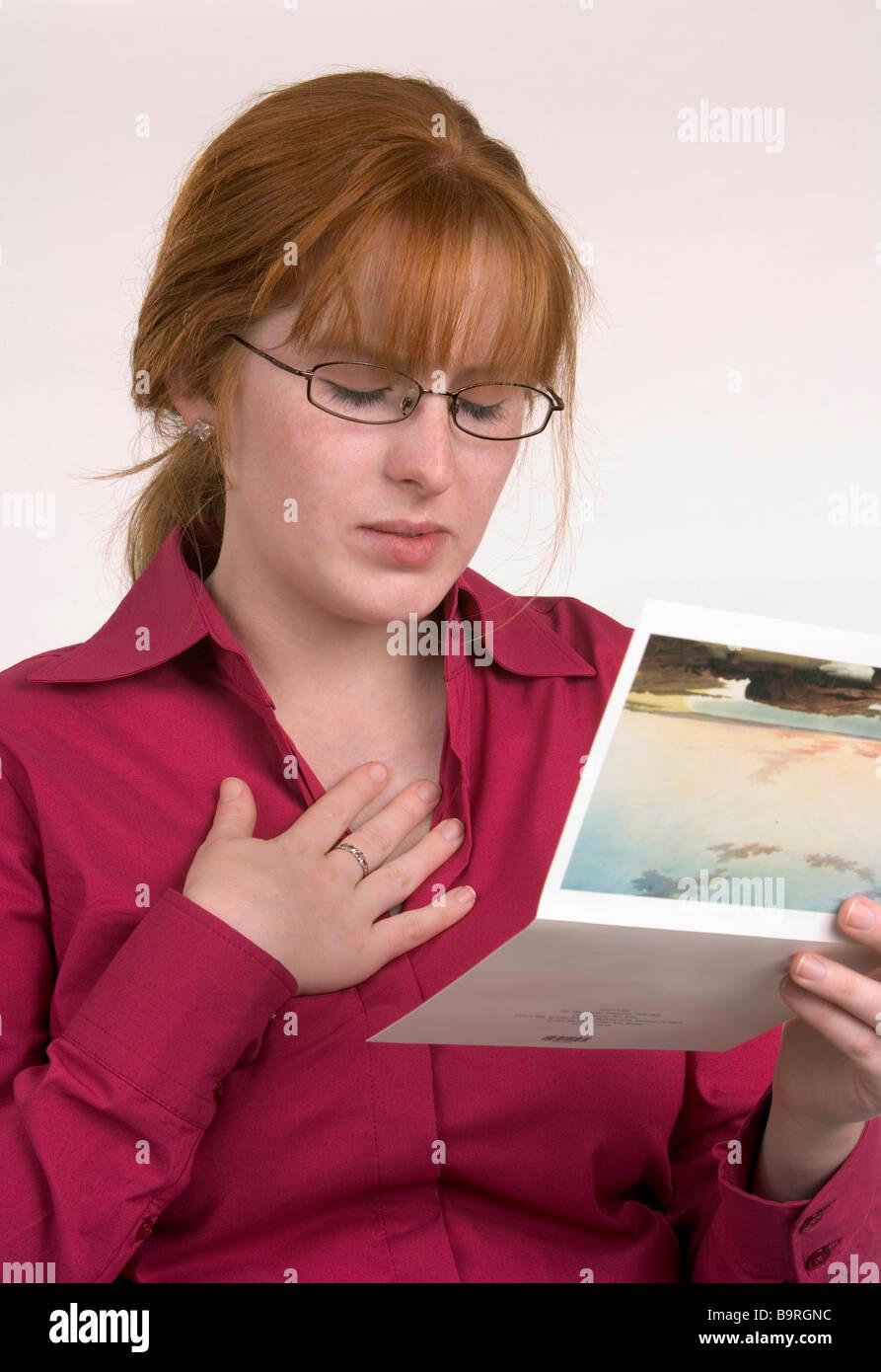 Eine Frau liest eine Karte, die einige Nachrichten übermittelt hat, die ihr traurig oder emotionale gemacht Stockbild