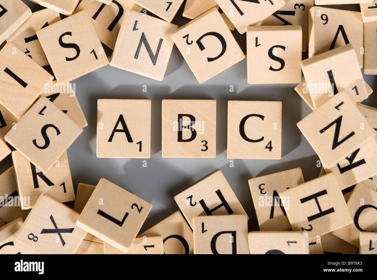 Scrabble-Stücke mit zahlreichen verschiedenen Buchstaben, ABC Stockbild